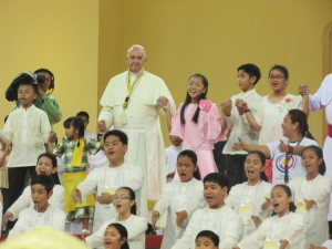 "Pope Francis joins children in dancing and singing ""Tell the World of His Love"" at the end of an encounter with the youth at the University of Santo Tomas (photo by JEREMAIAH OPINIANO / The Filipino Connection)"