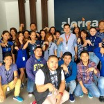 """Employees in the Lipa City """"mega facility"""" of Alorica Philippines flash the company's hand sign. Alorica, a US-based firm, is among ten business process outsourcing firms operating in the city, which remains among the ten Philippine """"next wave cities"""" for the BPO sector. (photo by Virgil Sam Jamili Catajoy III, posted on Alorica Philippines' Facebook page)"""