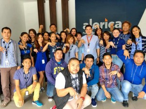 "Employees in the Lipa City ""mega facility"" of Alorica Philippines flash the company's hand sign. Alorica, a US-based firm, is among ten business process outsourcing firms operating in the city, which remains among the ten Philippine ""next wave cities"" for the BPO sector. (photo by Virgil Sam Jamili Catajoy III, posted on Alorica Philippines' Facebook page)"