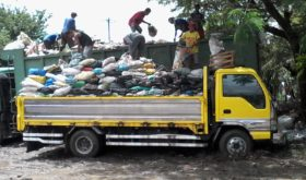 Garbage haulers from a barangay transfer trash from the barangay's own garbage truck to that of RC Bella Waste Management and Disposal Services. (photo by Marlon Alexander Luistro / The Filipino Connection)